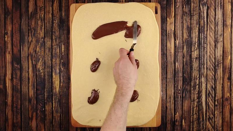 tas de Nutella déposés sur une pâte à gâteau avec une spatule