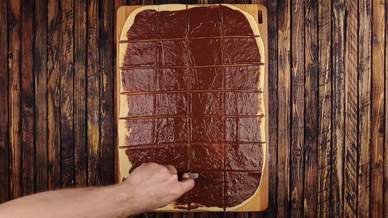 pâte recouverte de Nutella coupée en carrés à l'aide d'un roulette à pizza