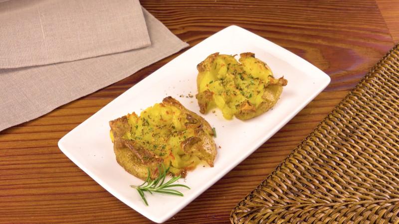 deux écrasés de pommes de terre cuits et présentés dans une assiette rectangulaire