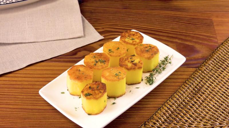 des pommes de terre cuites et en forme de cylindre présentées sur une assiette rectangulaire
