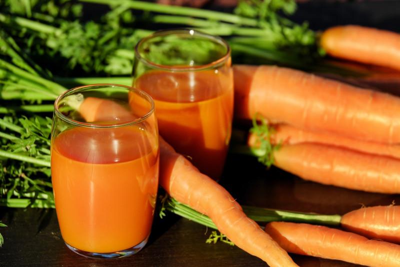verres remplis de jus de carotte et des carottes posées à côté
