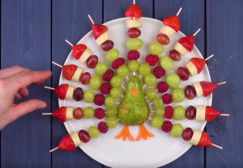 paon en fruits avec poire, raisins, framboises, bananes, fraises