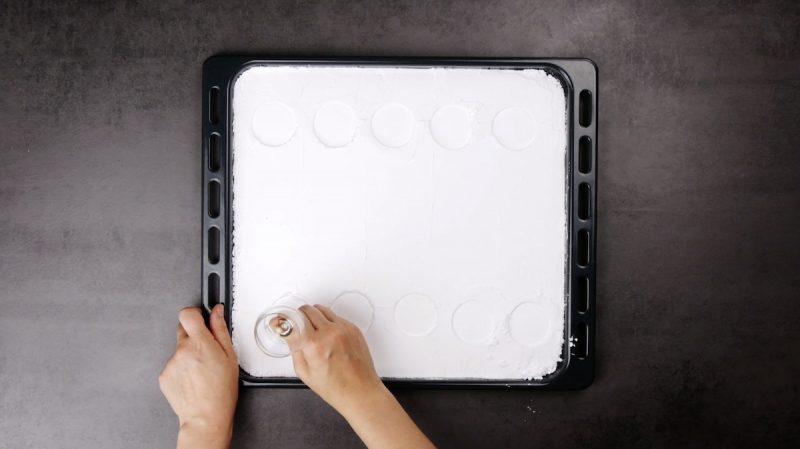 sucre glace sur plaque à pâtisserie avec des ronds formés par un verre à pied