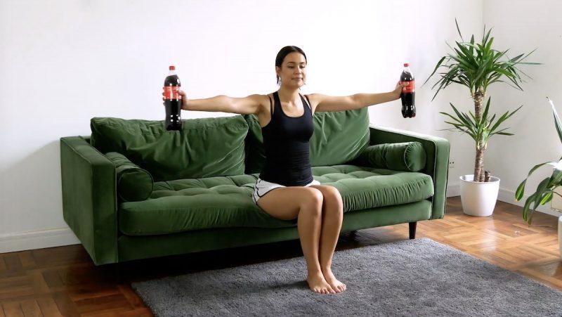 Prenez une bouteille dans chaque main et asseyez-vous sur le bord du canapé. Tendez les bras de chaque côté