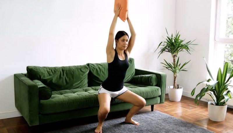 Prenez un coussin. Mettez-vous devant le canapé, les jambes un peu plus écartées que la largeur des hanches. Placez le coussin entre vos mains et déplacez-le au-dessus de votre tête avec les bras tendus, tout pliant les jambes pour arriver à la même hauteur que l'assise du canapé, sans la toucher. Répétez l'exercice 20 fois.