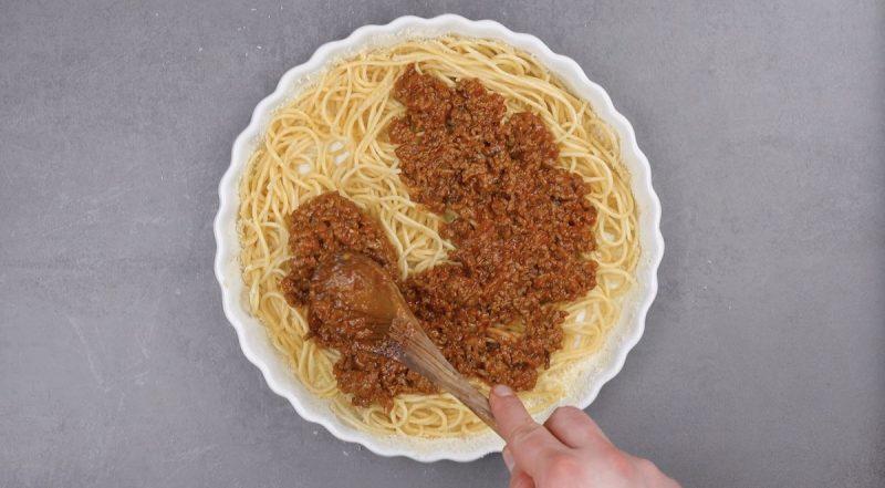 sauce bolognaise sur les spaghettis dans un moule à tarte