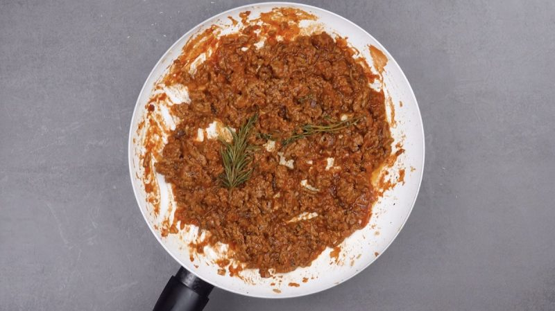 sauce bolognaise qui mijote dans une poêle avec des branches de romarin et de thym