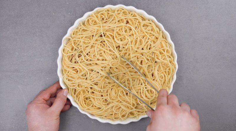 des spaghettis sont déposés par-dessus la bolognaise dans le moule à tarte
