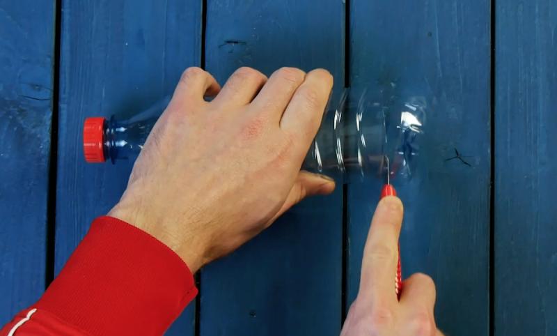 Couper le fond d'une bouteille en plastique avec un cutter