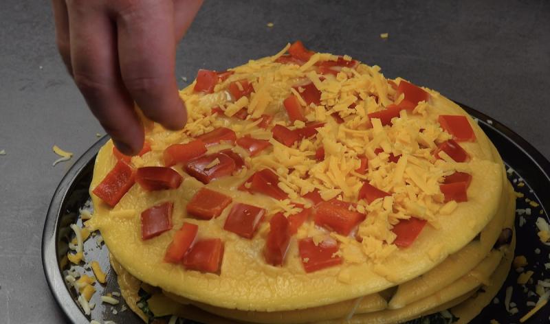 omelette aux poivrons rouges saupoudrée de cheddar