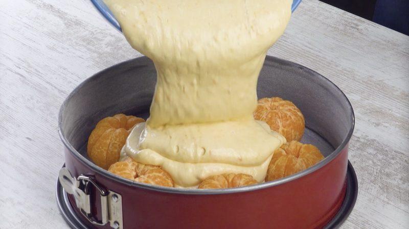 pâte à gâteau versée sur les mandarines dans un moule à charnière