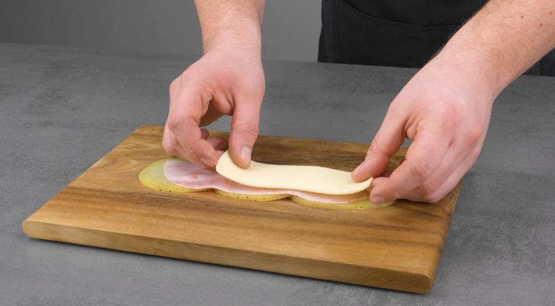 tranches de jambon et fromage posées sur les pommes de terre
