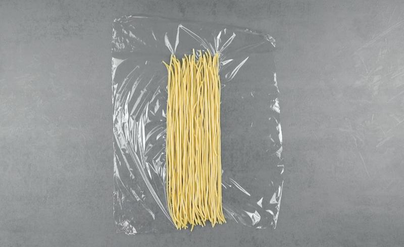 spaghettis mis côte à côte sur un morceau de film alimentaire