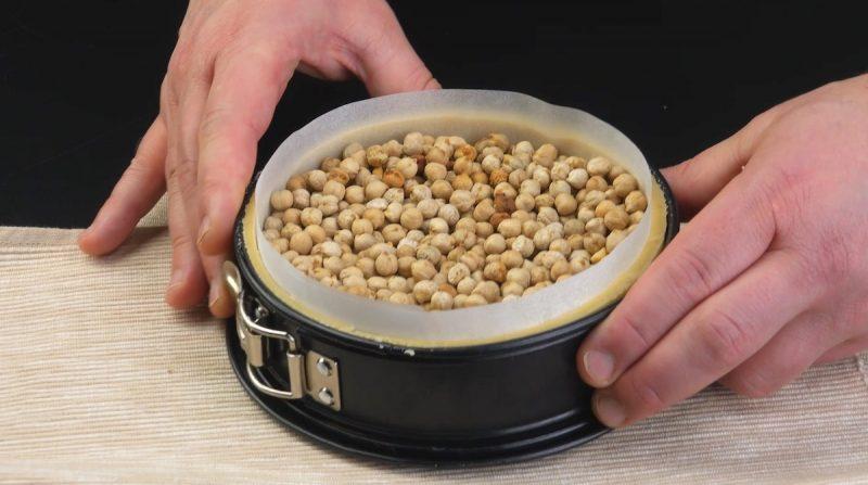 ajouter du papier sulfurisé et remplir le moule de pois secs