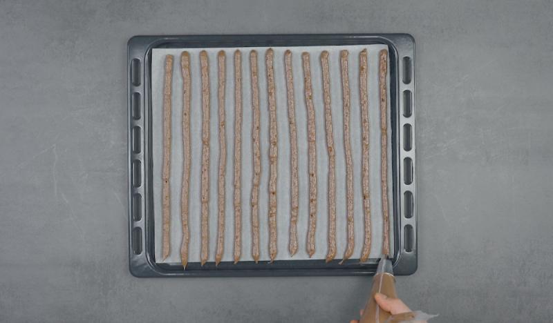 bandes de meringue au chocolat sur plaque à pâtisserie