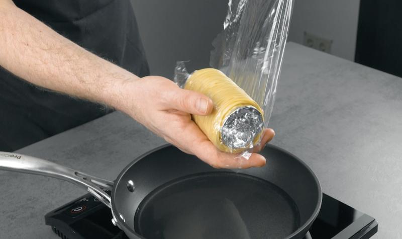 spaghettis enroulés autour du rouleau de papier toilette recouvert d'aluminium et le film plastique est retiré