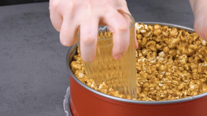 pop-corn au caramel pressez dans le fond et les bords d'un moule à charnière à l'aide d'un verre