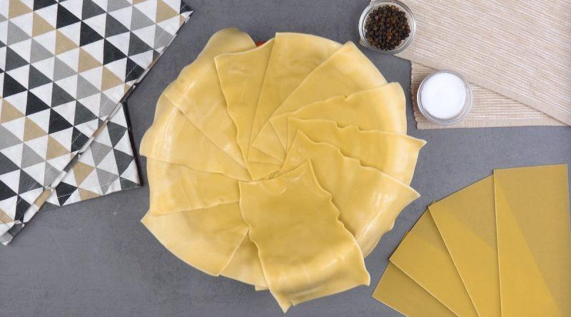 feuilles de lasagnes cuites déposées dans le fond et le bord d'un saladier allant au four