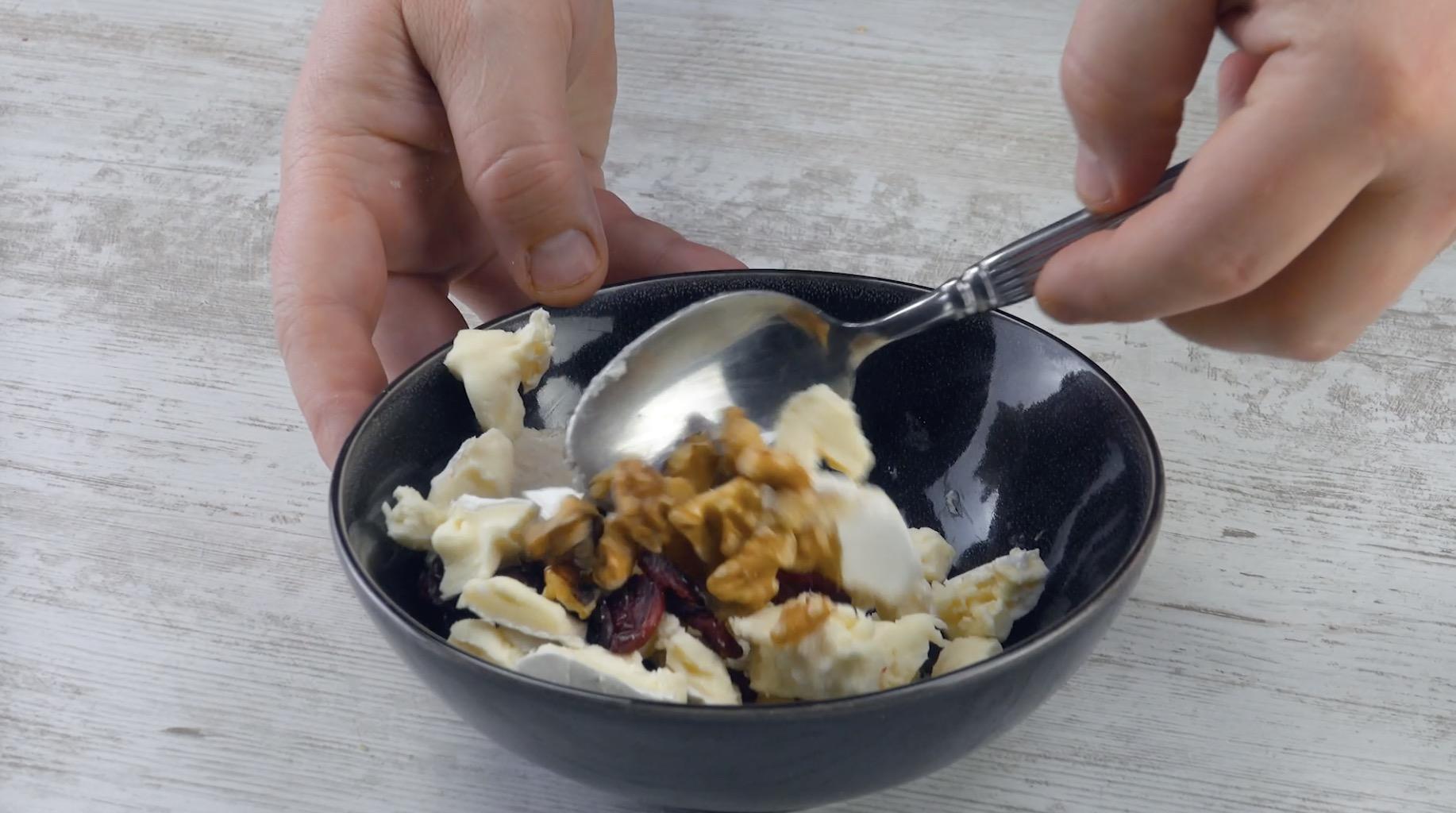 mélanger des morceaux de camembert avec des noix et des canneberges