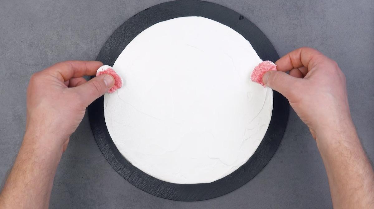 mettre 2 morceaux de guimauve rouge aux extrémités du gâteau recouverts de glaçage blanc