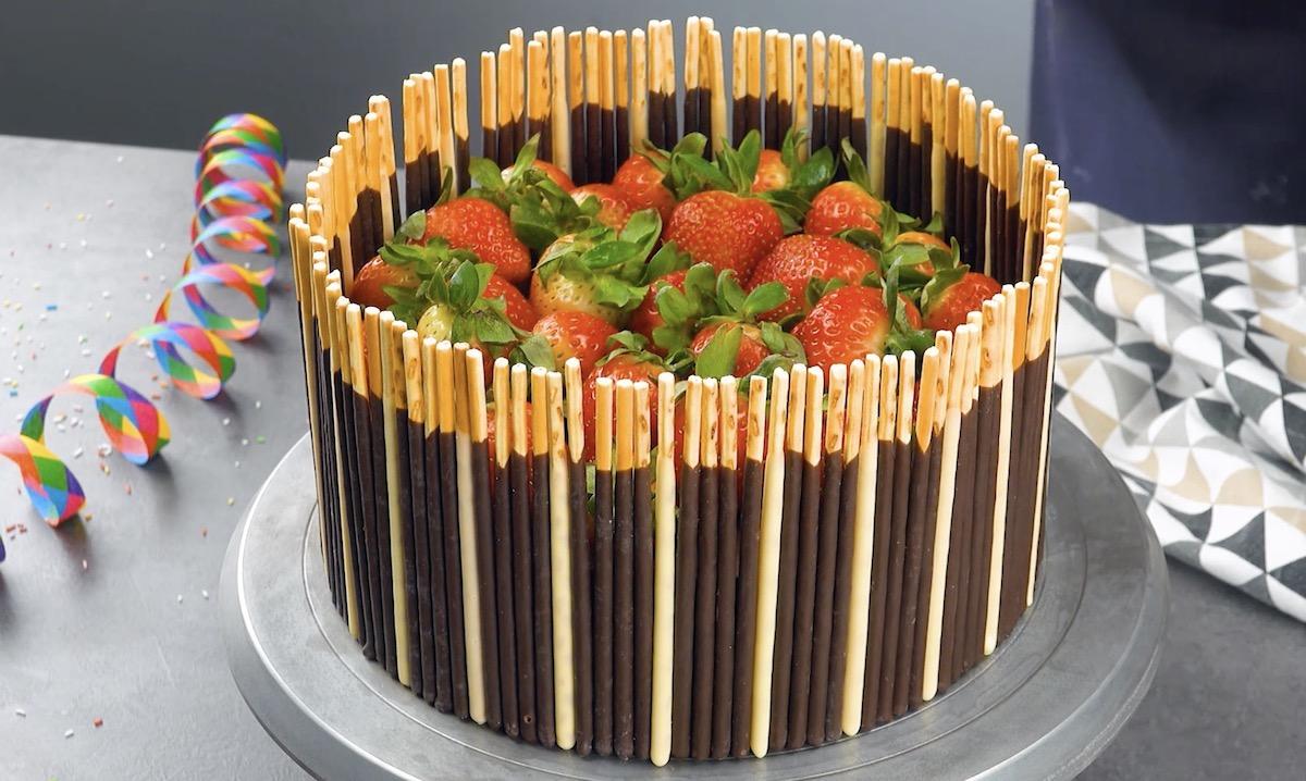 mettre les mikados autour du gâteau enduit de ganache et le décorer avec des fraises