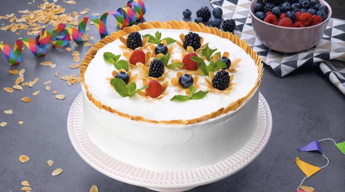 gâteau décoré avec des baies, des amandes et des feuilles de menthe