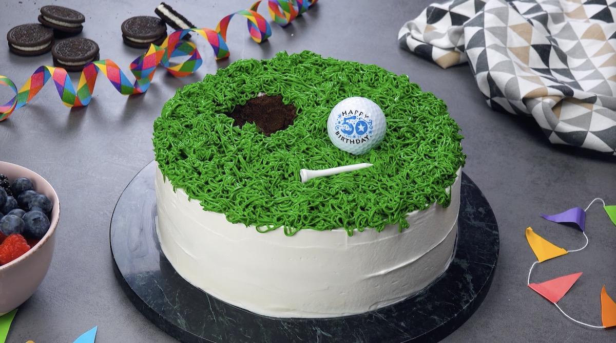 mettre du glaçage vert sur le gâteau et le décorer avec une balle de golf et un tee