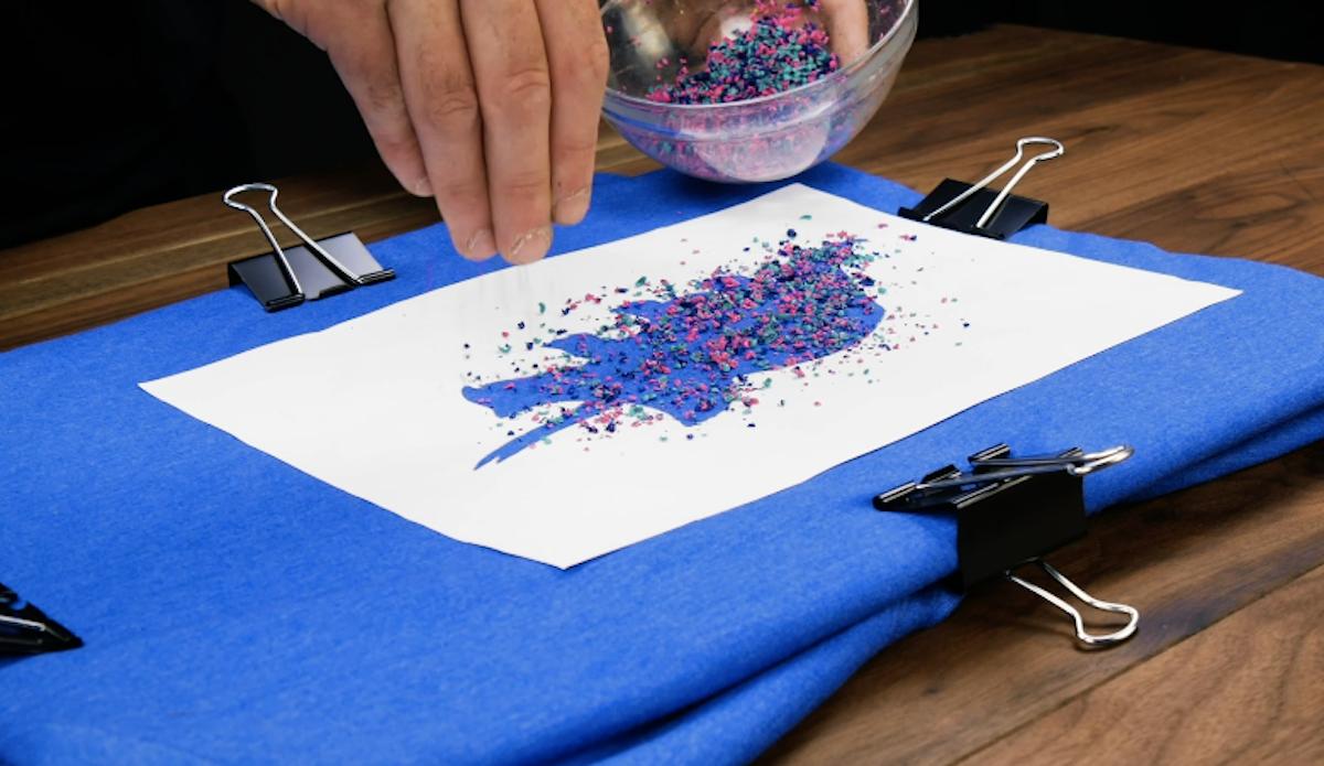 Placez la feuille sans le motif sur le T-shirt et saupoudrez-la avec les crayons de cire râpés.