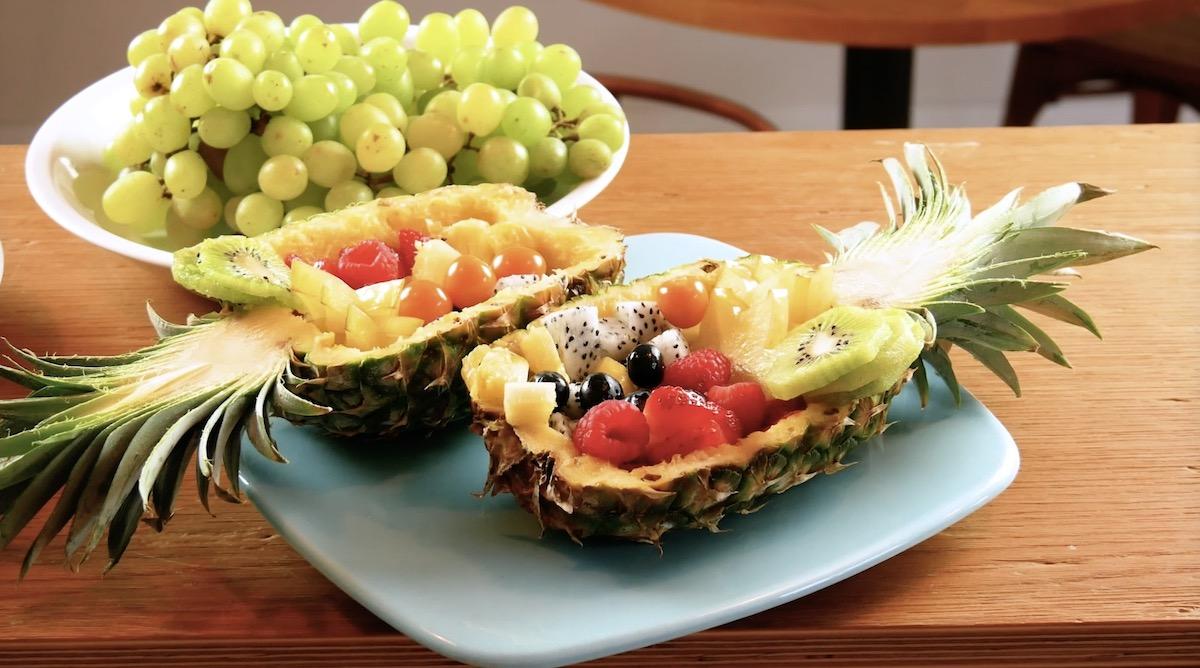 salade de fruits servie dans des moitiés d'ananas