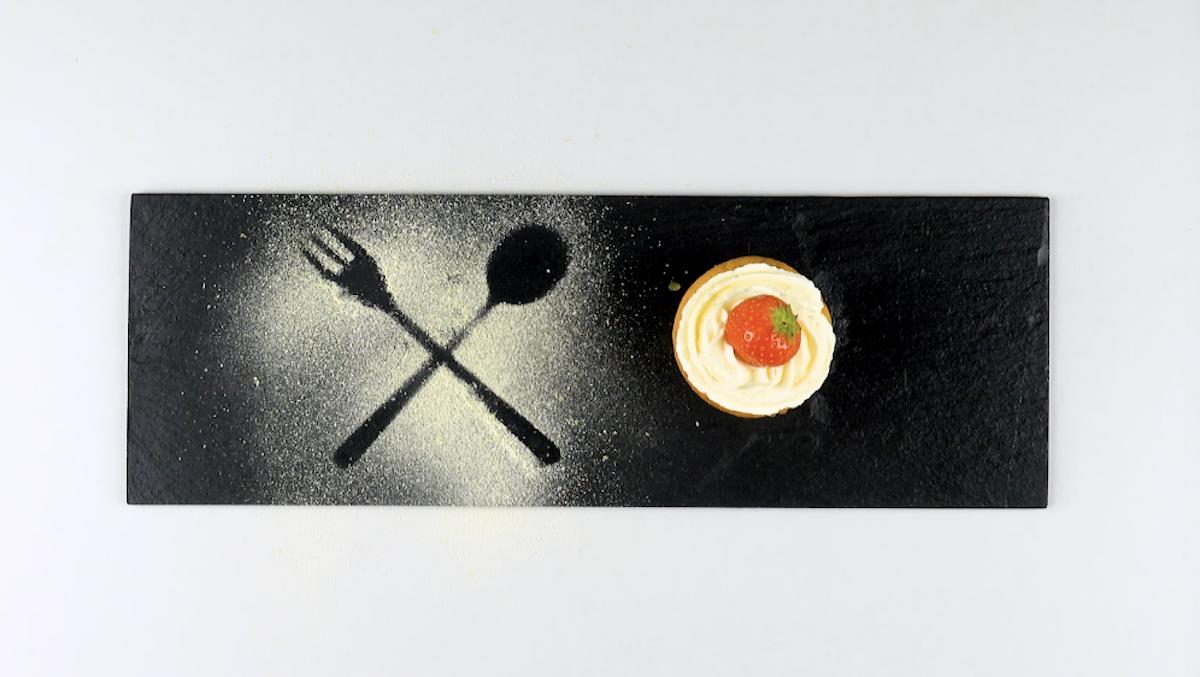 forme de fourchette et cuillère en poudre de sucette sur une assiette sombre