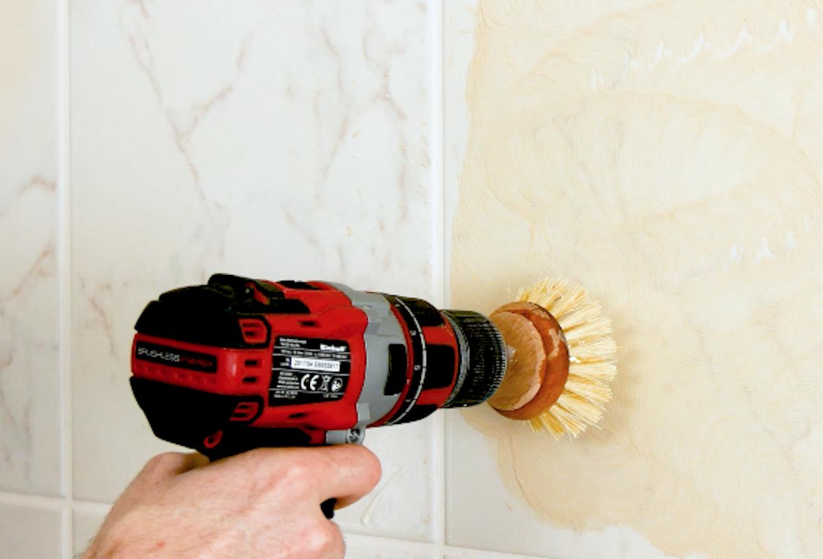 nettoyage de mur avec une brosse sur une perceuse