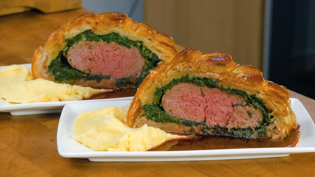 2 tranches de bœuf wellington servies sur assiettes avec de la purée et de la sauce