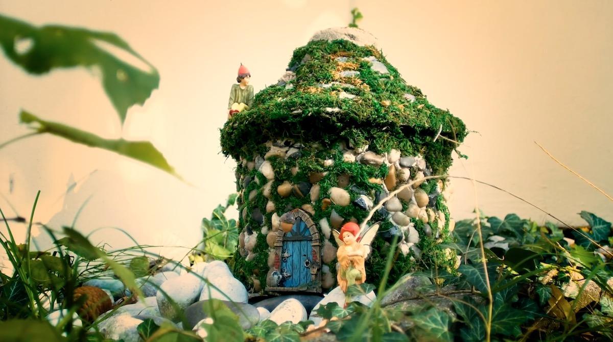 petite maison fabriquée avec une bouteille en plastique, des cailloux et de la mousse