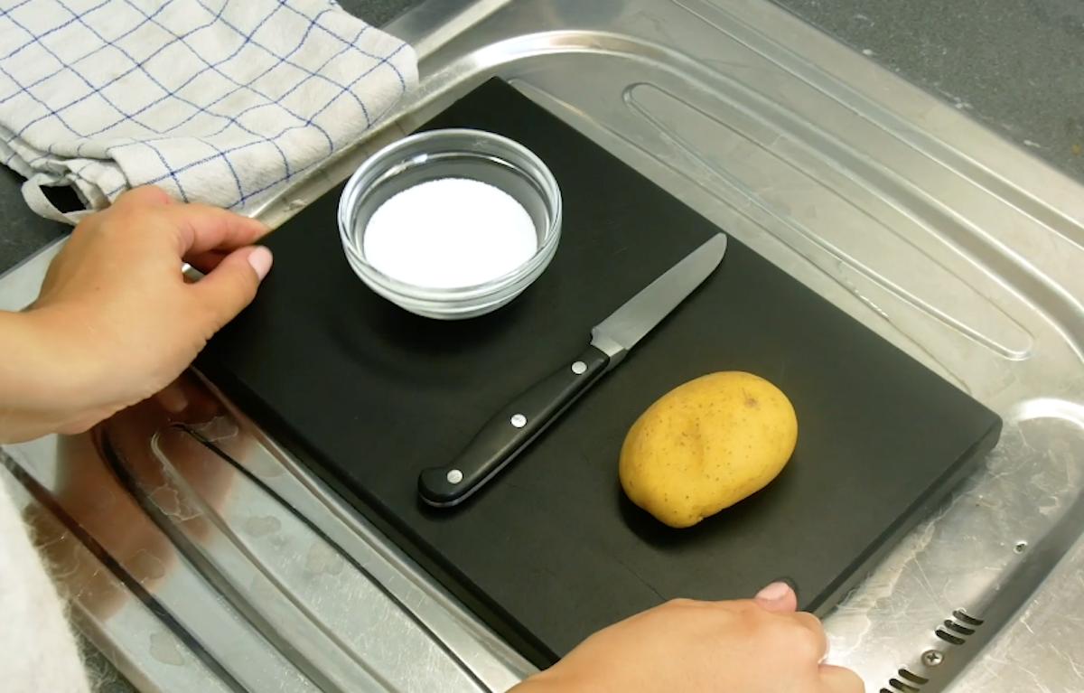 bol de sel, couteau et pomme de terre sur un plateau