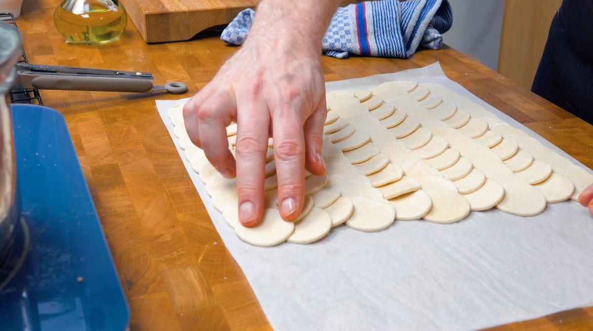 mettre les cercles de pâte sur du papier sulfurisé et les badigeonner de blanc d'œuf