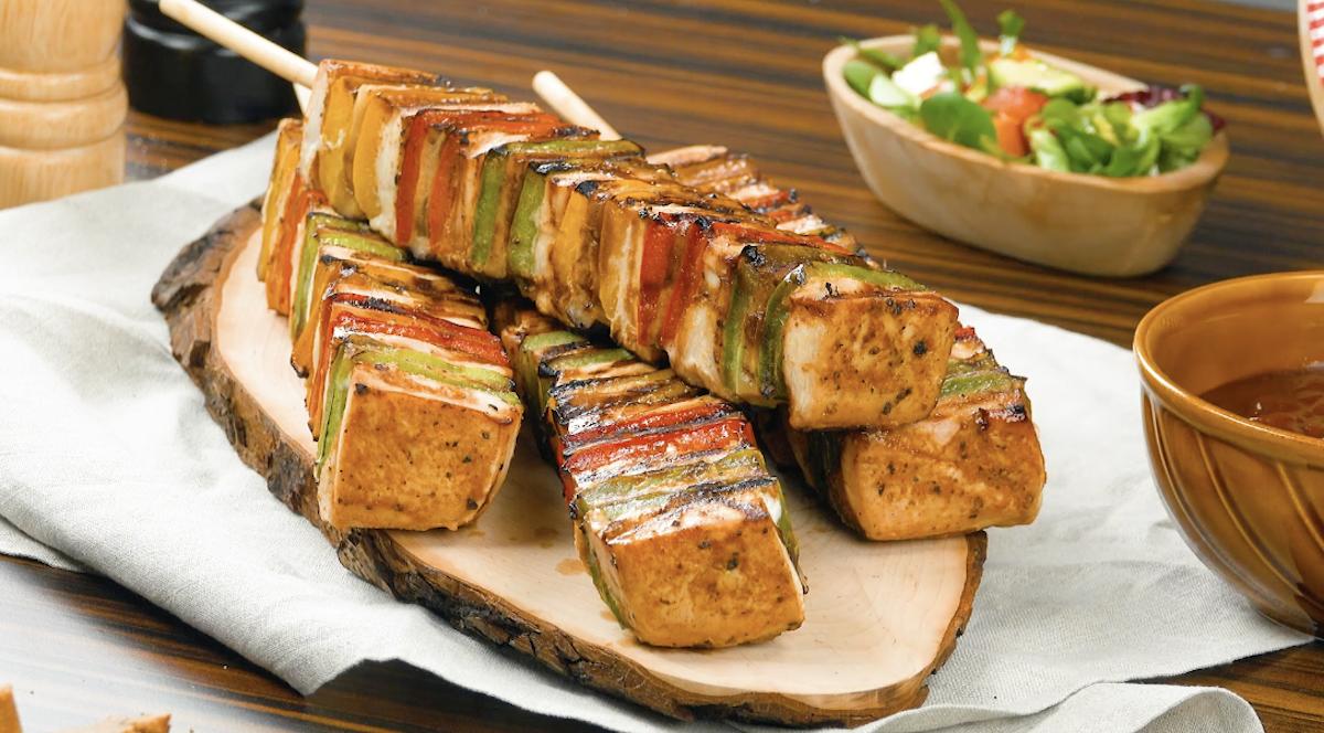 4 brochettes de poulet grillées sur un plat