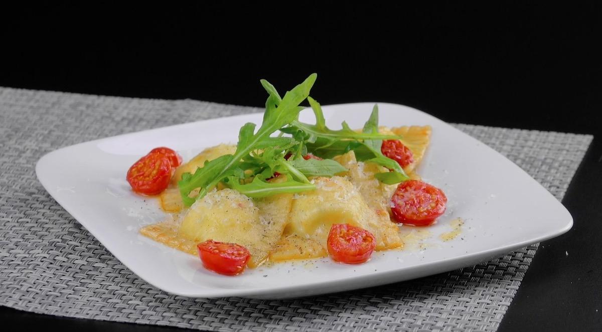raviolis sur assiette accompagnés de roquette et de tomates