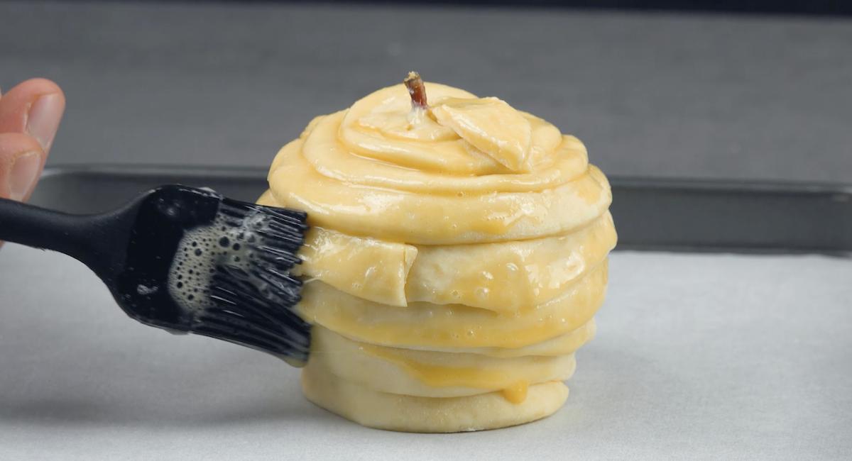 enrouler la pomme de pâte feuilletée et la badigeonner d'œuf
