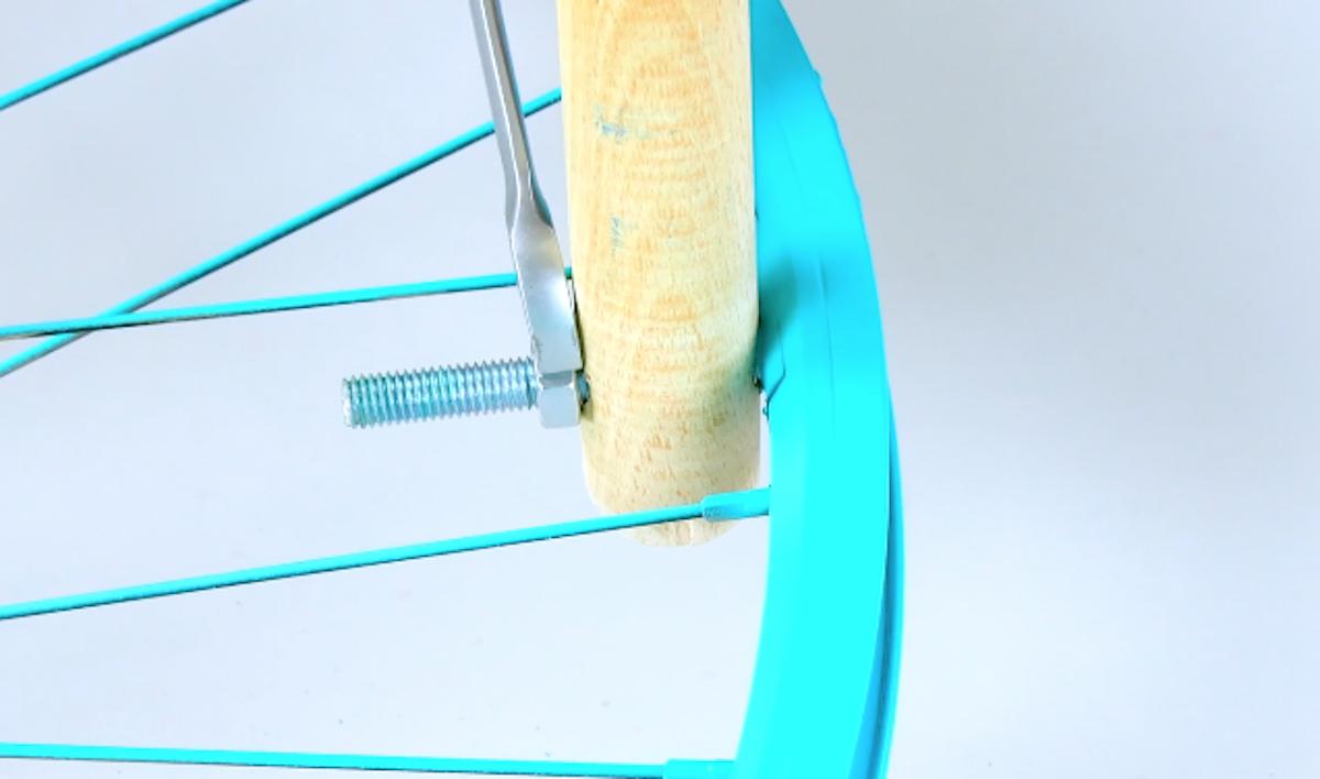 Fixez les 4 manches avec les tiges filetées et les écrous dans les trous percés au préalable dans la jante