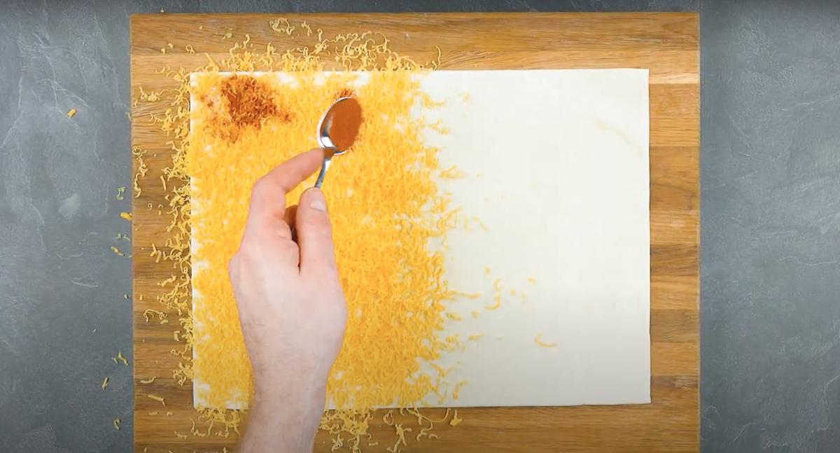 râper le fromage sur la pâte feuilletée