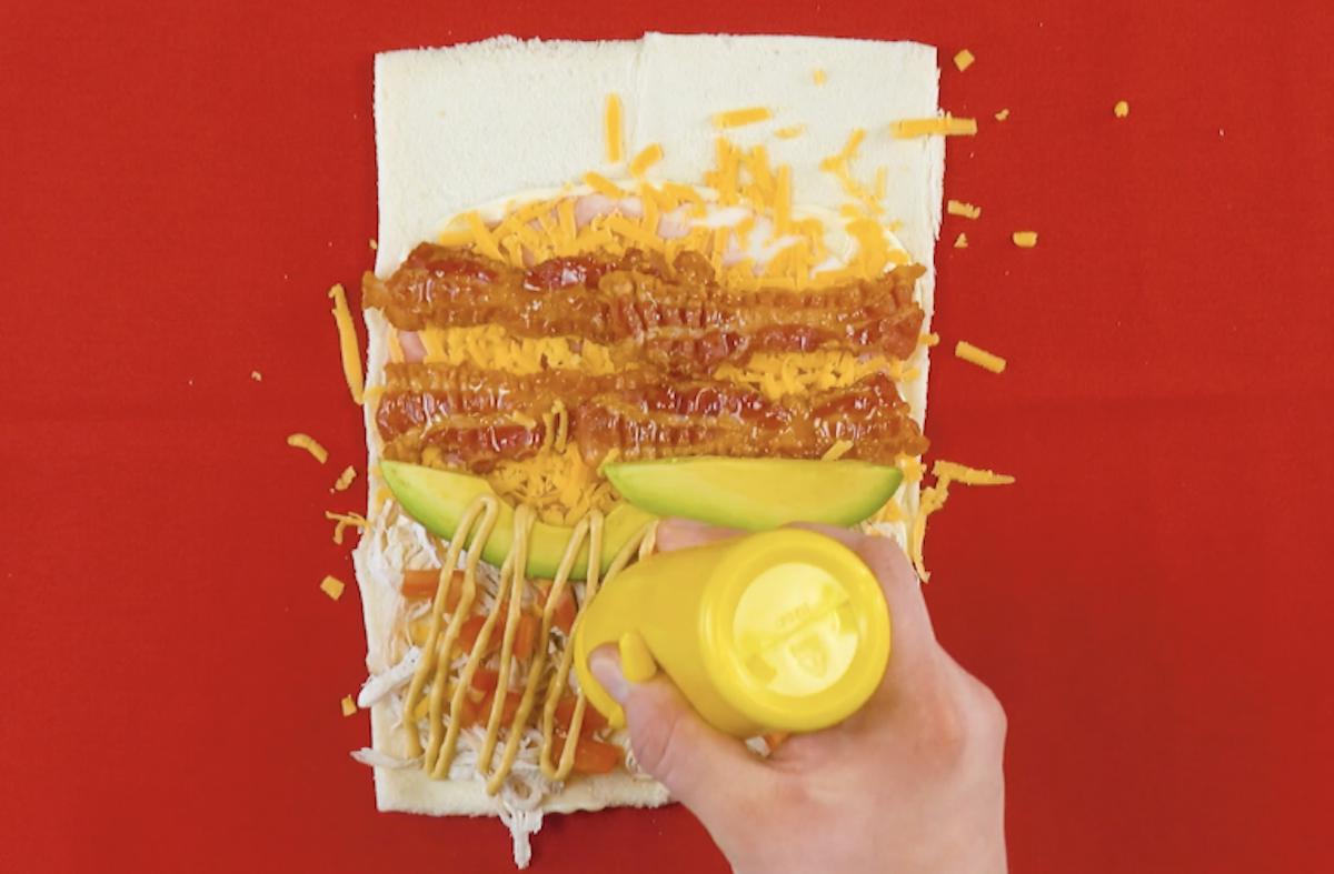 garnir le tout de jambon cuit, de cheddar, de bacon, d'avocat, de tomates et de moutarde