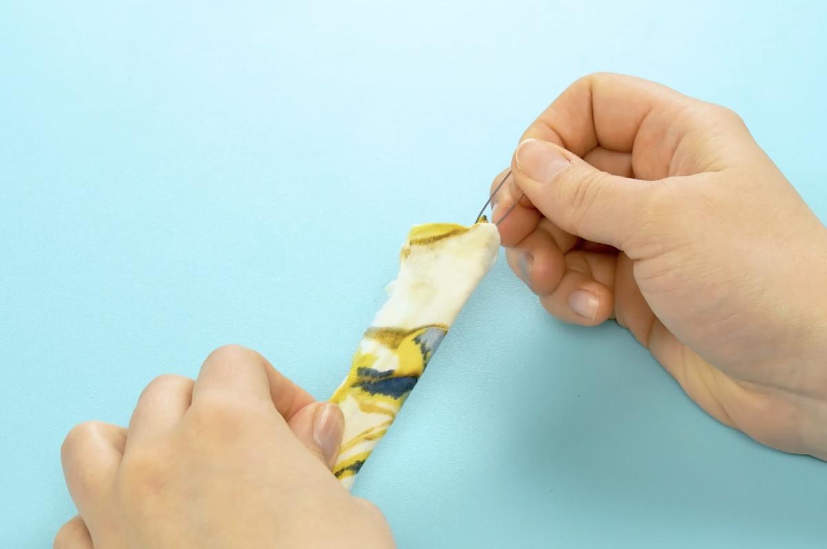 planter une épingle à nourrice à l'extrémité de chaque tube et tirez-la à travers le tube, en retournant le tissu