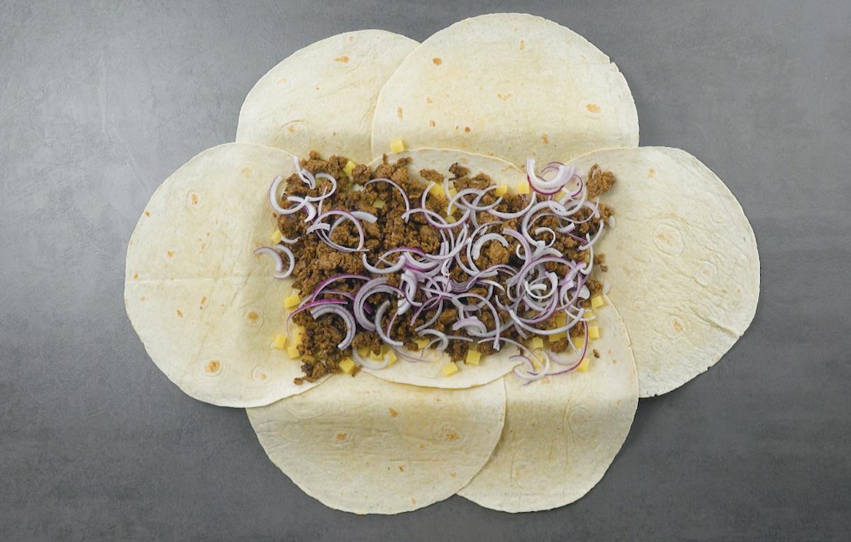 repartir les pommes de terre, la viande hachée et les oignons rouges sur les tortillas